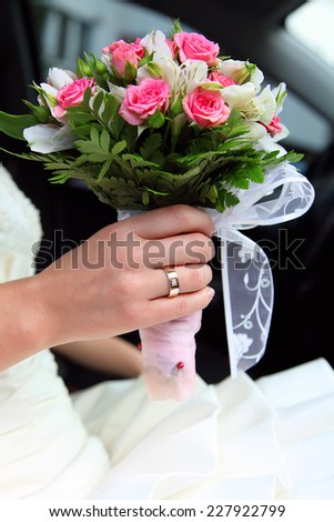 bride holds wedding bouquet of roses