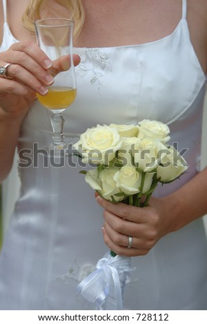 Bride holds wedding flowers with ring and cocktail