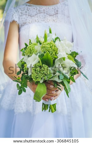 Bride holds wedding green bouquet in rustic style - stock photo