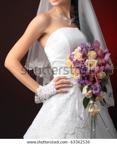 Bride in a designer dress holding a rose bouquet. - stock photo