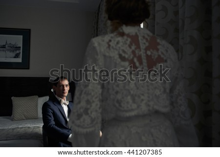 Bride in a dress with lace flowers looks at a groom while he sits in the chair