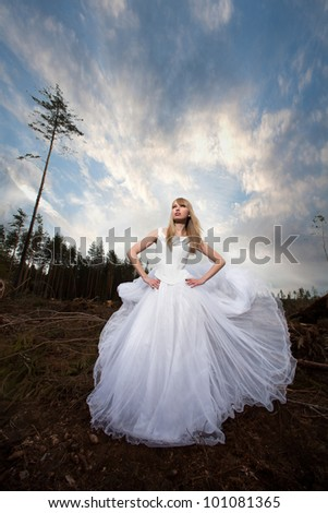 bride in a gorgeous white dress among the fairy forest - stock photo