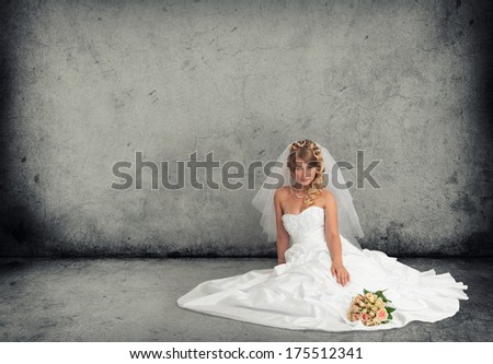 bride in a wedding dress on a gray concrete floor - stock photo