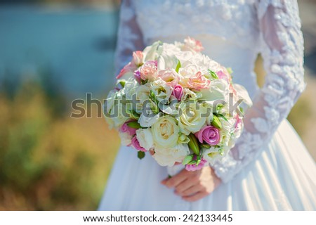 Bride in a white dress in summer green park with a bouquet in hand.