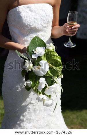 Bride in a white wedding dress holding a beautiful bouquet of flowers and a glass of alcohol - stock photo