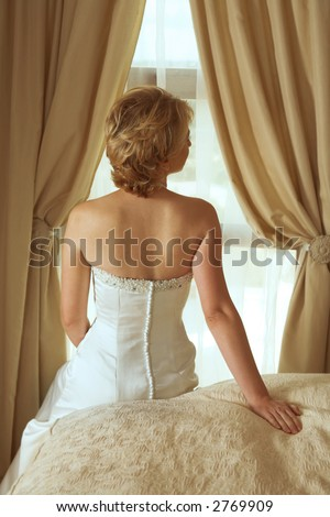 bride in beautiful pearl beaded white dress with short blond hair sitting on the bed in her bedroom - stock photo
