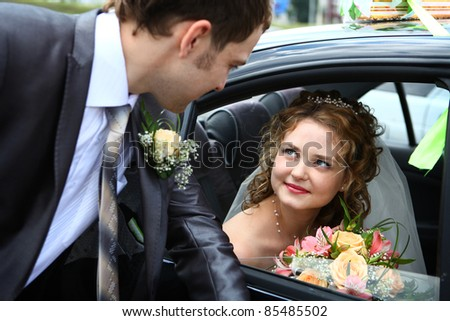Bride in car and groom - stock photo