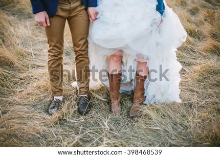 Bride in cowboy boots and groom in brown shoes stand side by side at sunset field. Shallow focus. - stock photo