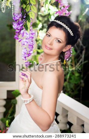 Bride in garden with white dress, summer. Brunette - stock photo