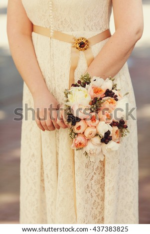 Bride in peach dress holds a wedding bouquet of pink flowers