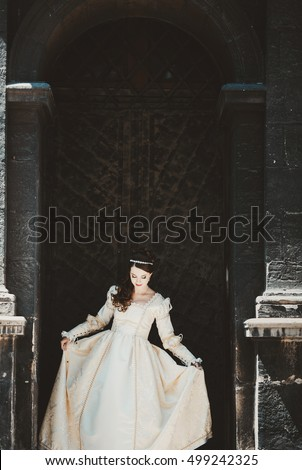bride in royal wedding dress stands near the old gate