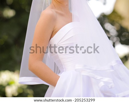 bride in sating dress holding hand in pocket