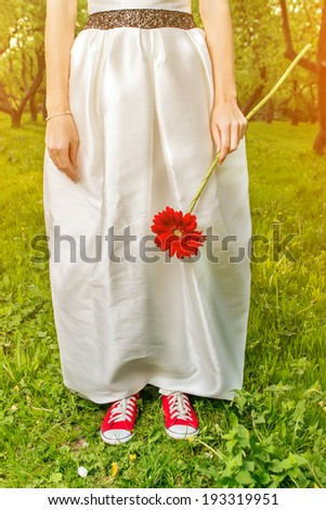 Bride in sneakers holding a flower in summer park  - stock photo
