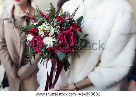 Bride in the fur coat holds red wedding bouquet