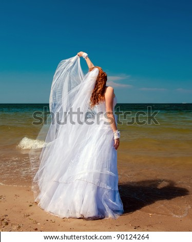Bride in the wind. Pretty lady in a wedding dress on sea.