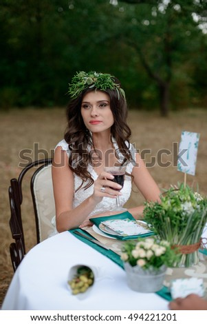 Bride in wedding dress sits in a garden on a chair  decorated table.