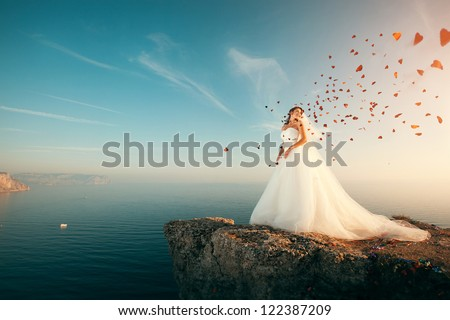 Bride in wedding dress stands on a cliff with a beautiful sea view from the top and flying confetti in the shape of hearts - stock photo