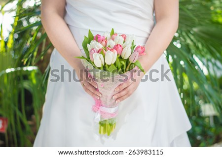 Bride in wedding dress with flower bouquet with tulips in her hands - stock photo