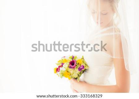 Bride in wedding gown hiding behind veil  - stock photo