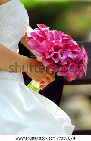 Bride in wedding gown holding bouquet of pink flowers - stock photo