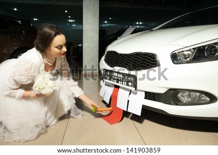 bride in white dress feeding a car with carrot - stock photo