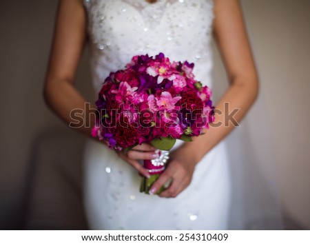 Bride in white dress holding a wedding bouquet. - stock photo