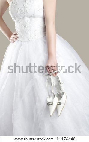 bride in white dress with shoes in her hand - stock photo