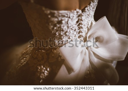 Bride in white ribbon dressed, vintage color and selective focus on dress.