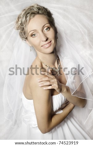 Bride in white veil looking at camera and smiling. Portrait. Fashion wedding shot.