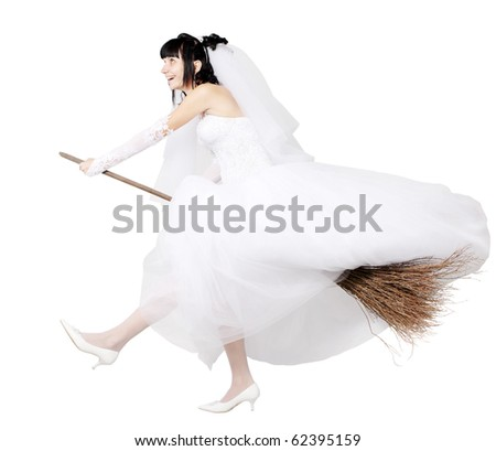 bride in white wedding dress on a broom - stock photo