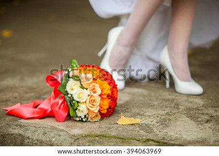 Bride in white wedding dress preparing to her wedding standing near bouquet of summer flowers showing her legs and shoes - stock photo