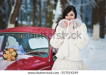 Bride  in winter near old vintage car - stock photo