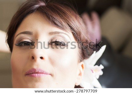 Bride is getting professional make up for her wedding day,almost done . - stock photo