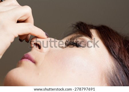 Bride is getting professional make up for her wedding day, putting on eyeliner. - stock photo