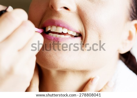 Bride is getting professional make up for her wedding day, putting on lip gloss. - stock photo