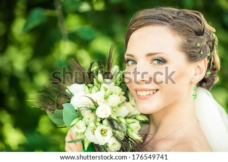 Bride is holding a bouquet near her cheek. Soft focus. - stock photo