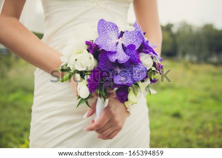 Bride is holding a bouquet of lilac in the hands on a green background - stock photo