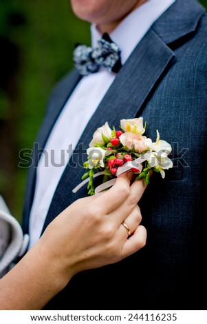 Bride is holding a groom's boutonniere