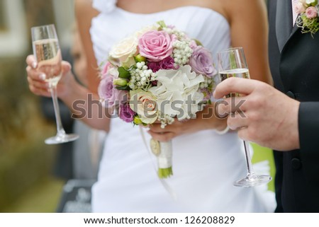 Bride is holding a wedding bouquet and a glass of champagne - stock photo