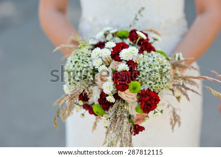 Bride is holding beautiful bright wedding bouquet. - stock photo