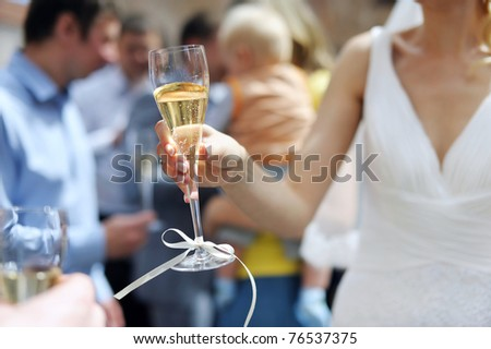 Bride is holding champagne glass after a wedding ceremony - stock photo