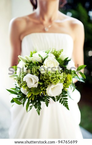 Bride is holing wedding flowers. Focus on flowers. - stock photo