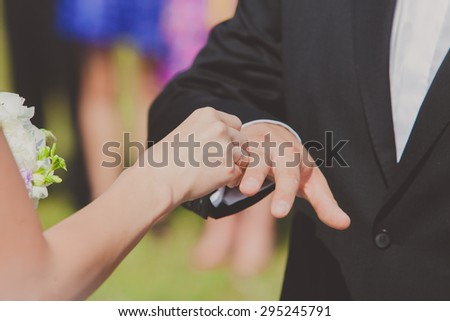 Bride is putting a ring on groom's finger. Wedding ceremony - stock photo