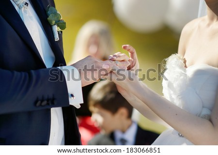 Bride is putting wedding ring on groom's finger - stock photo