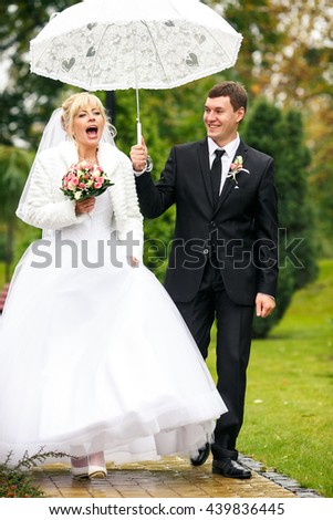 Bride laughs walking under an umbrella held by a groom