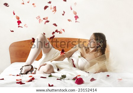 bride lays on a bed. Petals of roses from above fall - stock photo