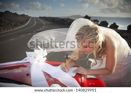 Bride leaning over the hood of the machine, writes a letter, road in the background. - stock photo