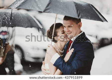 Bride leans to groom's shoulder smiling while they walk across the street in rain - stock photo
