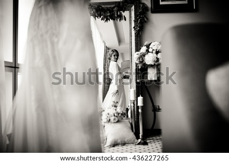 Bride looks at her back in the mirror decorated with bouquets and pillows - stock photo