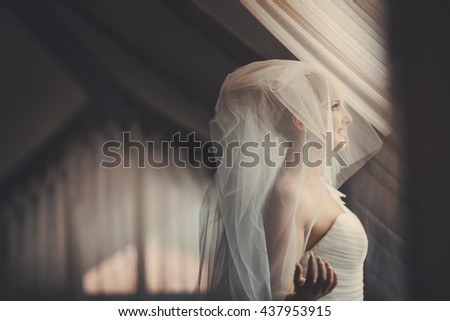 Bride looks up through the window posing in the hotel room - stock photo